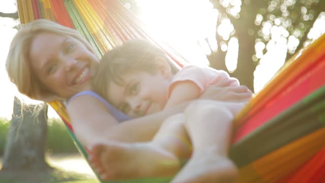 Mother and young son relaxing together in hammock