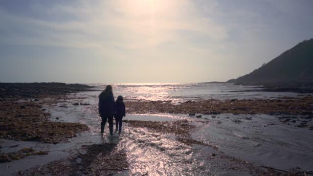 vídeos y material grabado en eventos de stock de mother and young son walking along the shore - cornwall inglaterra