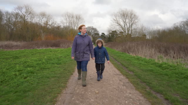 Mother and young son walking in a park
