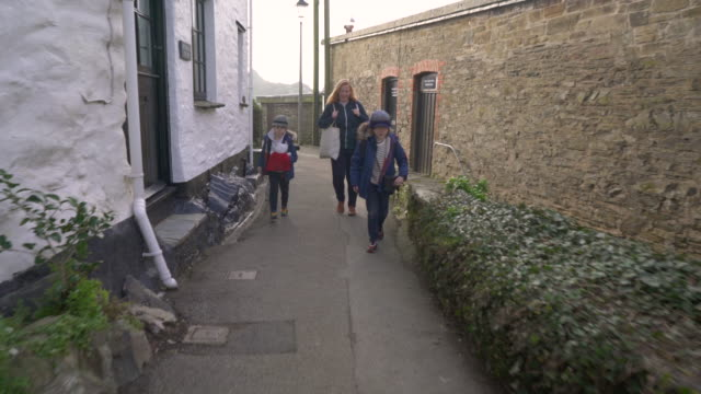 mother and young sons heading home from holiday cottage - village stock videos & royalty-free footage