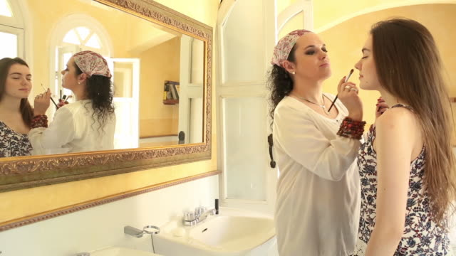 Mother applies makeup to young Latina woman, in bathroom