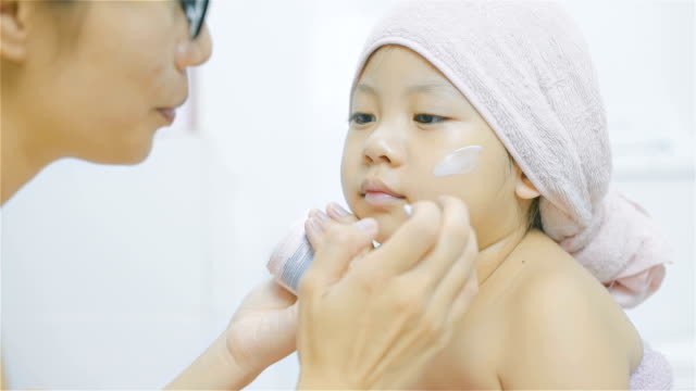 Mother applying cream on her daughter's face in bathroom