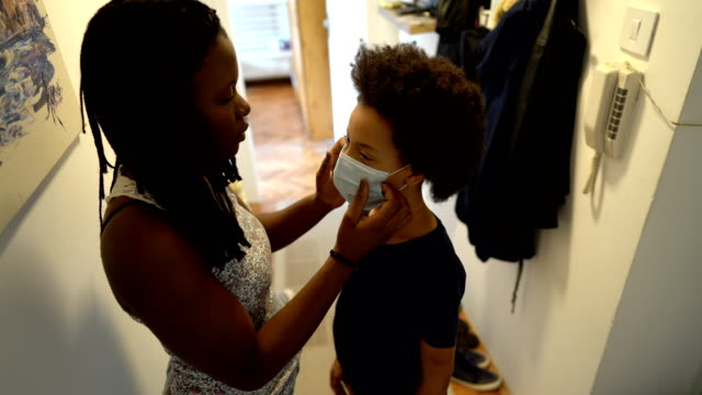 mother applying face protective mask to her daughter - primary age child stock videos & royalty-free footage