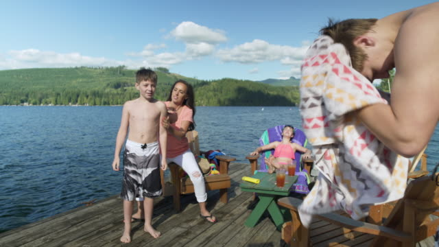 mother applying sun cream to son by lakeside, family sunbathing in background, lake connaught, washington, usa. - sonnencreme stock-videos und b-roll-filmmaterial