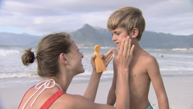 mother applying sun cream to son - sonnencreme stock-videos und b-roll-filmmaterial