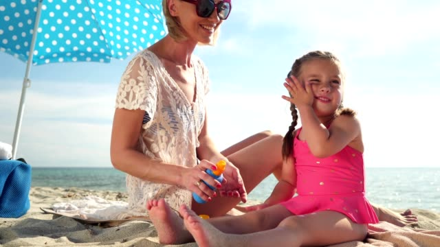 mother applying sun protection cream on her daughter - sun cream stock videos & royalty-free footage