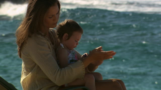 mother applying sunscreen to daughter at beach - see other clips from this shoot 1141 stock videos & royalty-free footage