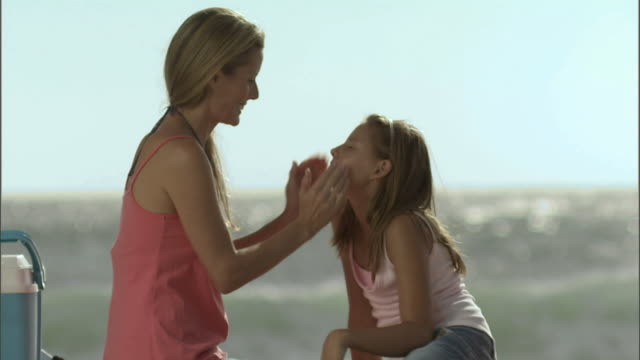 WS Mother applying sunscreen to daughter's face and shoulders as they sit on the beach/ Cape Town, South Africa