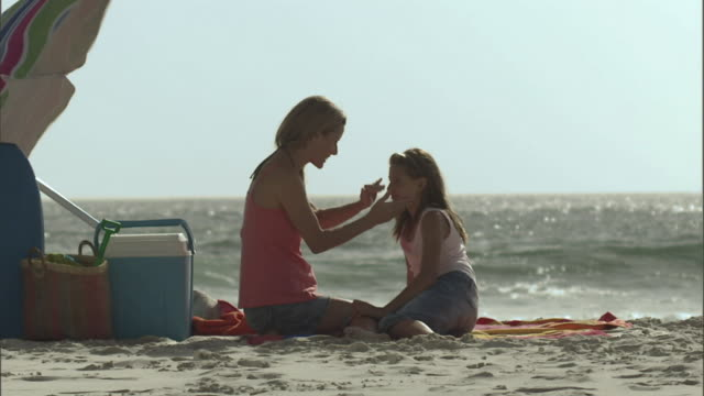 WS Mother applying sunscreen to daughter's face as they sit on the beach and waves break in the background/ Cape Town, South Africa