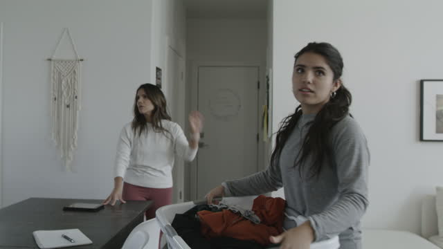 mother arguing with teenage girl carrying clothing in laundry basket / lehi, utah, united states - housework stock videos & royalty-free footage