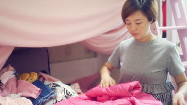 母は娘の服を手配する - 片付いた部屋点の映像素材/bロール