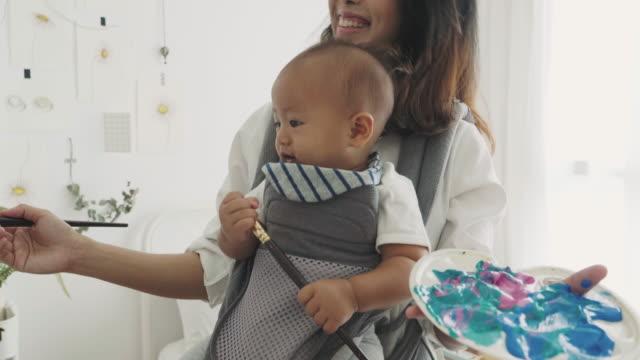 mutter künstler tun weile tragen ihr baby - carrying stock-videos und b-roll-filmmaterial