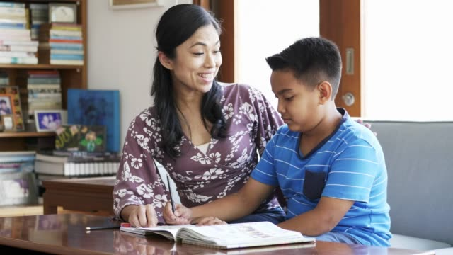 Mother assisting and cheering son while studying