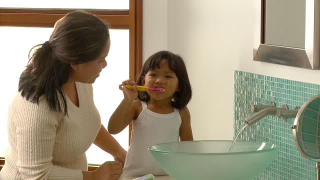 MS, Mother assisting daughter (2-3) brushing teeth in bathroom, Richmond, Virginia, USA
