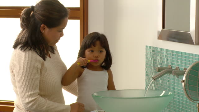 ms, mother assisting daughter (2-3) brushing teeth in bathroom, richmond, virginia, usa - brushing stock videos & royalty-free footage