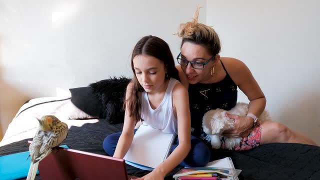 vidéos et rushes de mère aidant la fille pendant des activités scolaires. - young animal