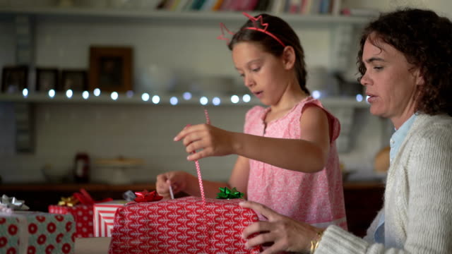 Mother assisting girl in wrapping christmas gifts