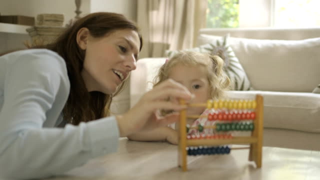 Mother assisting her daughter in counting abacus