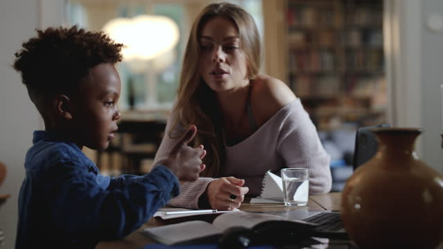 vidéos et rushes de mother assisting son in counting through fingers during homeschooling - famille monoparentale