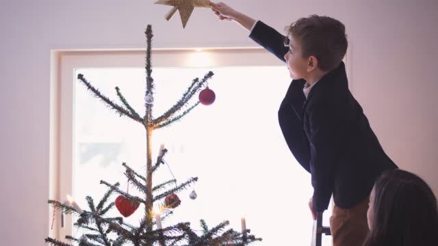mother assisting son in decorating christmas tree at home - christmas tree stock videos & royalty-free footage