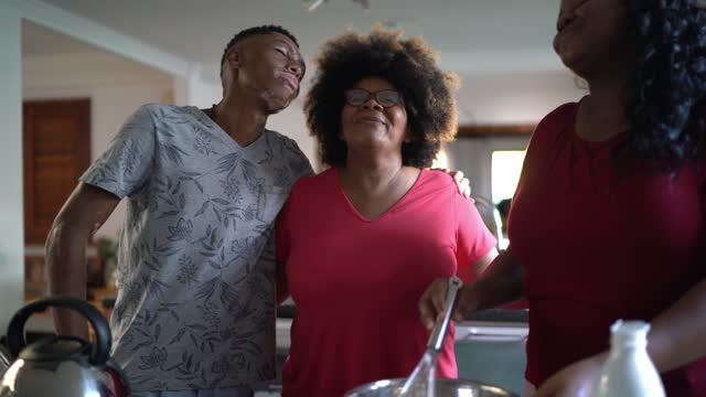 stockvideo's en b-roll-footage met moeder die cake met dochter en zoon thuis bakt - zoon