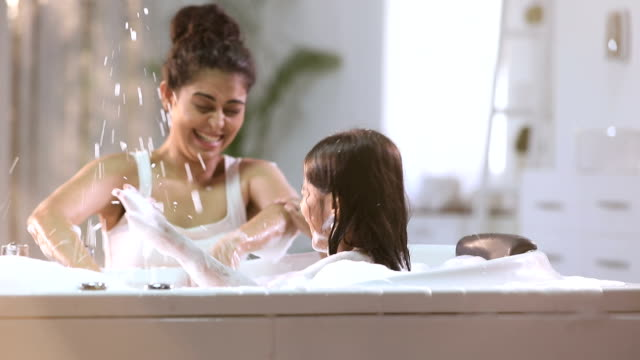 stockvideo's en b-roll-footage met mother bathing her daughter in bathtub, delhi, india - domestic bathroom