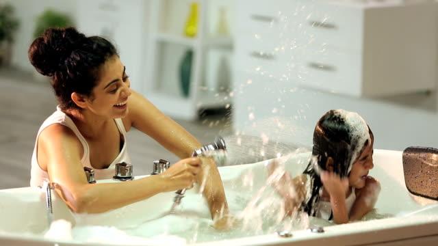 mother bathing her daughter in bathtub, delhi, india - kinder beim duschen stock-videos und b-roll-filmmaterial