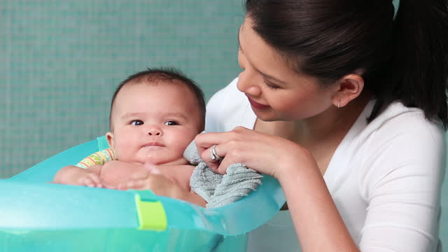 Mother bathing infant