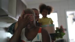 Mother being surprised by husband and son who are covering her eyes and holding a gift for mother's day / birthday