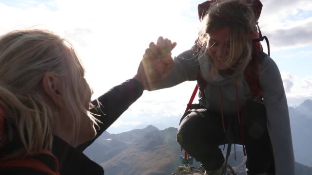 mother belays daughter to summit of mountain, they exchange 'high-fives' - safety stock-videos und b-roll-filmmaterial