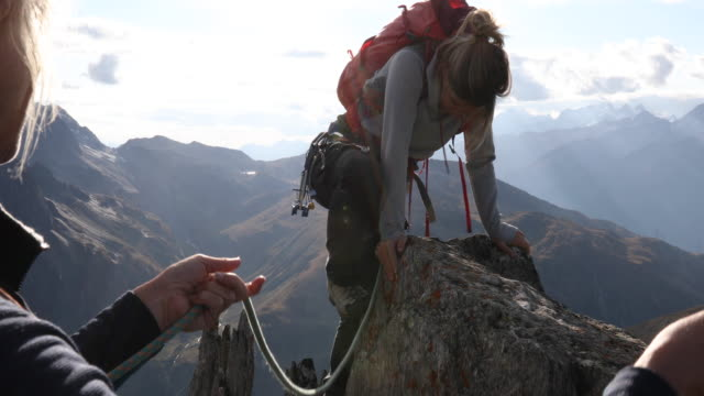 mother belays daughter to summit of mountain - erholung stock-videos und b-roll-filmmaterial