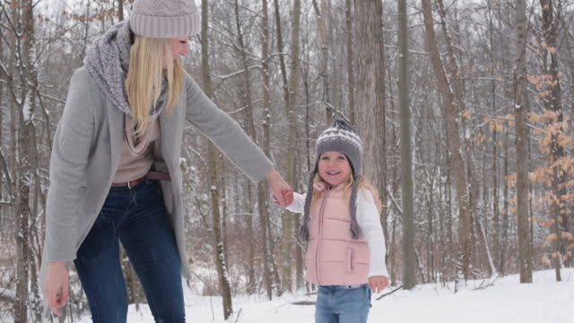 mother bending over to kiss daughter on a snow covered trail - bending over stock videos & royalty-free footage