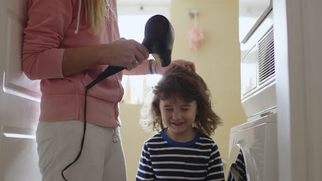 mother blow cold air with a hair dryer to her three year old son - tumble dryer stock videos & royalty-free footage