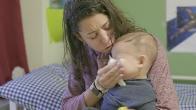 vídeos de stock, filmes e b-roll de mother blowing sick baby son's nose. - assoando nariz