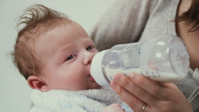 stockvideo's en b-roll-footage met cu mother bottle feeding baby boy (2-5 months), brussels, belgium - zuigfles