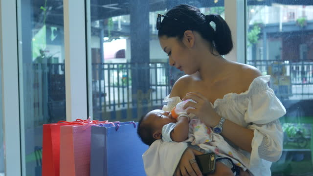 Mother bottle feeding milk for baby in shopping mall