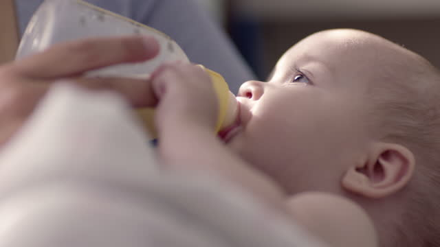 vidéos et rushes de mother bottle nursing baby - maternelle