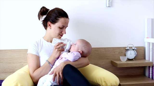 stockvideo's en b-roll-footage met hd: mother bottle-feeding her baby - zuigfles