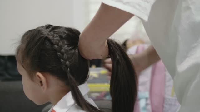 vídeos de stock e filmes b-roll de mother braiding daughter's hair before to school. - vestir camiseta