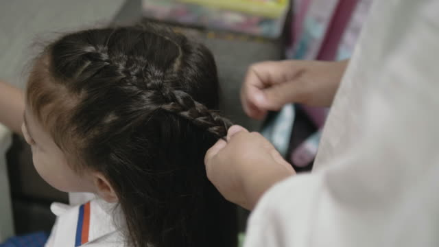 mother braiding daughter's hair before to school. - braided hair stock videos and b-roll footage