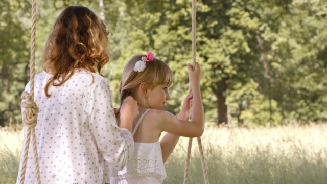 slo mo mother braiding daughter's hair on a swing - slovenia meadow stock videos & royalty-free footage