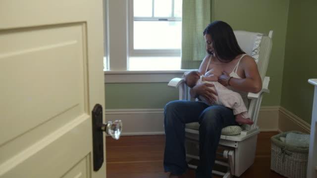 stockvideo's en b-roll-footage met ms pan mother breastfeeding baby daughter (3-5 months) in rocking chair / seattle, washington state, usa - schommelen schommelstoel