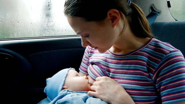 mother breastfeeding her baby in the car - breastfeeding stock videos & royalty-free footage