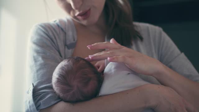 Mother breastfeeding her little baby girl