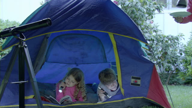 ms mother bringing cookies to girl (8-9) and boy (10-11) lying in tent in garden, encino, california, usa, td tu - zelt stock-videos und b-roll-filmmaterial