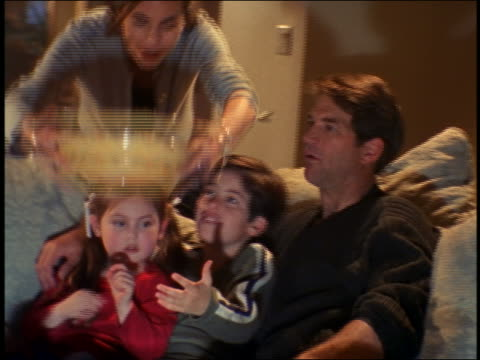 vidéos et rushes de mother bringing out large bowl of popcorn to family on couch watching tv - 1990 1999