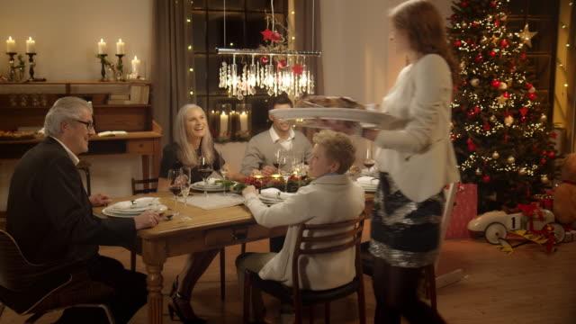 vídeos de stock, filmes e b-roll de mãe traz o jantar de família sentada na mesa de natal - irmão