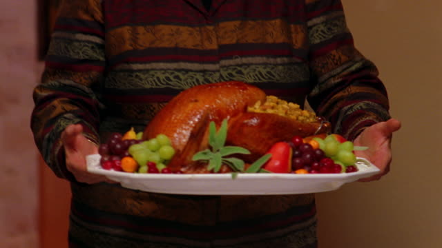 A mother brings the Thanksgiving turkey to the table.