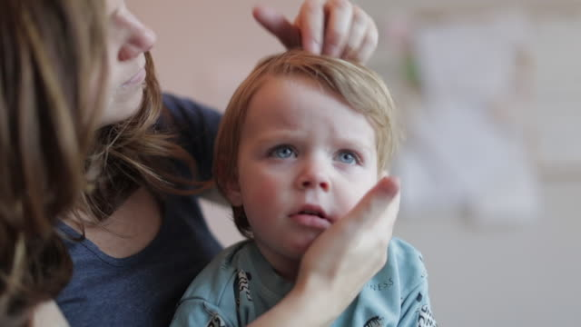 stockvideo's en b-roll-footage met mother brushes her young son's hair - casual clothing
