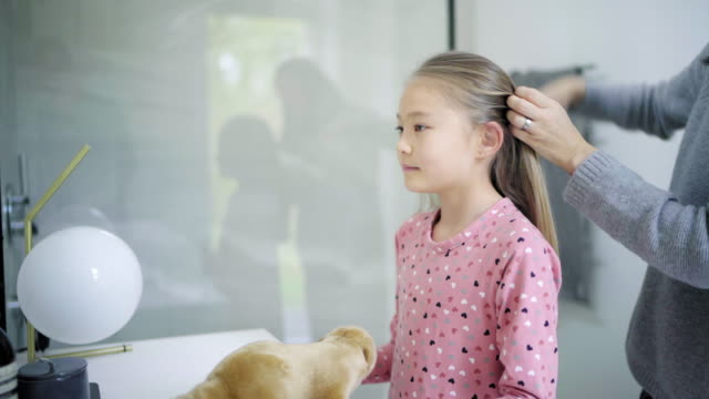 stockvideo's en b-roll-footage met mother brushing daughter's hair - haarborstel